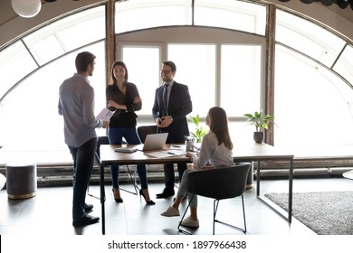 Happy diverse colleagues discussing project, sharing ideas at meeting in modern office, smiling employees enjoying pleasant conversation, brainstorming, involved in briefing, teamwork concept