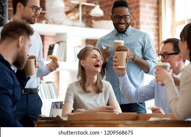 Happy diverse colleagues have fun at lunch break in office, smiling multiracial employees laugh and talk eating pizza and drinking coffee, excited workers celebrate shared win ordering takeaway food