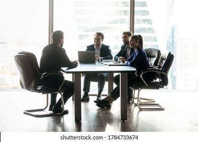 Happy diverse colleagues hr team sitting at table in front of male candidate, enjoying holding job interview in office. Full length motivated male seeker making good first impression on employers.