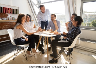 Happy diverse colleagues spend work break together eating takeaway delivery pizza in office, smiling multiracial employees have fun, laugh and chat, celebrating at workplace tasting Italian fastfood