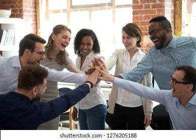 Happy diverse colleagues team people give high five together celebrate great teamwork result motivated by business success victory loyalty unity concept, good corporate relations and teambuilding