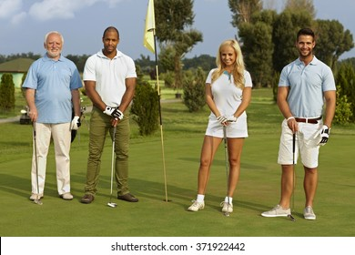 Happy diverse companionship standing on the green, ready to play, smiling, looking at camera.