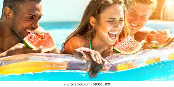 Happy diverse culture friends eating watermelon at swimming pool party - Young people having fun in summer Ibiza holidays - Friendship and tropical concept  - Focus on center girl - Warm filter