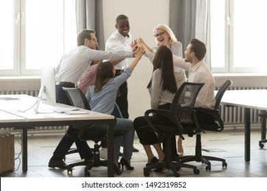 Happy diverse employees sitting in circle, giving high five at business briefing in office, smiling colleagues engaged in team building activity, celebrating achievement, business win or good result