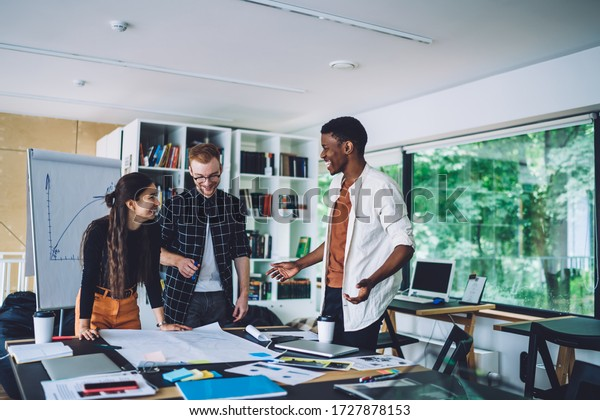 Happy diverse employees talking to each other and laughing while standing at table with papers and devices and takeaway coffee in modern office during meeting