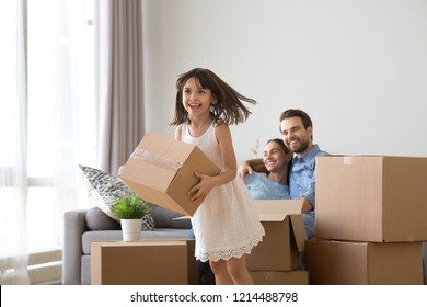 Happy diverse family in living room at new house. Cheerful active little daughter helps parents carrying carton boxes belongings at moving day. Buy new home or remodeling, loan and mortgage concept