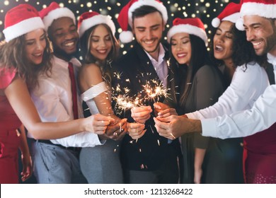 Happy diverse friends in New Year eve holding sparkling bengal lights, celebrating together, closeup