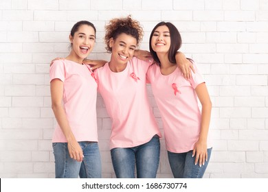 Happy Diverse Ladies In Pink Breast Cancer T-Shirts Hugging Posing Over White Brick Wall Background. Oncology Awareness Concept
