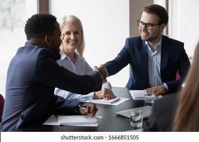 Happy diverse male colleagues handshake greeting get acquainted at business meeting in office, smiling young businessmen shake hands closing deal making agreement after successful negotiations