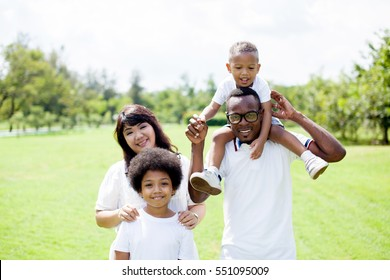 Happy diverse and mixed race family group photo in the park.