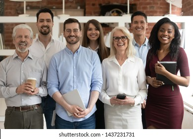 Happy diverse professional business team stand in office looking at camera, smiling young and old multiracial workers staff group pose together as human resource, corporate equality concept, portrait