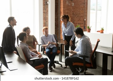 Happy diverse staff listens middle aged friendly business coach hold notepads pen writing thoughts ideas information people gather at corporate training, mentoring teamwork and office meeting concept