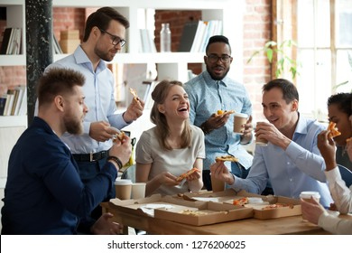 Happy diverse team people talking laughing at funny joke eating ordered pizza in office, friendly employees group enjoy positive emotions sharing lunch together having fun at work break on friday - Shutterstock ID 1276206025