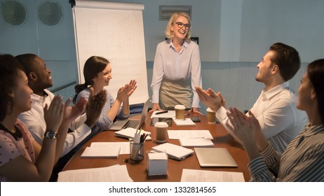 Happy diverse team people young employees interns applaud thank old happy mentor coach for good presentation training celebrating success support leader congratulating, appreciation gratitude, late