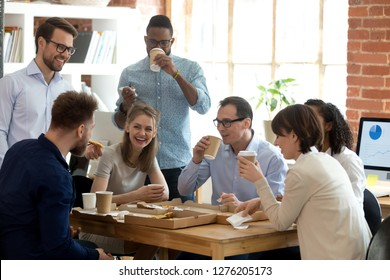 Happy diverse team talking having fun drinking coffee eating pizza together, multi-ethnic employees group enjoy takeaway food friendly conversation share lunch chatting laughing at office work break