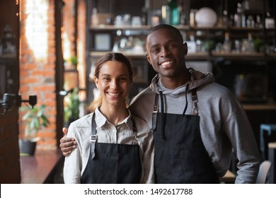 Happy diverse waiter and waitress looking at camera, smiling african male mixed race female two cafe colleagues stand in restaurant, millennial business team wear apron posing in coffee shop portrait