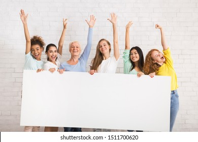 Happy Diverse Women Holding Blank White Board Waving Hello With Hands Against White Brick Wall Indoor. Mockup