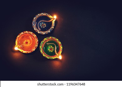 Happy Diwali background  - Colorful Clay Diya lit during Deepavali festival on black background, top down view