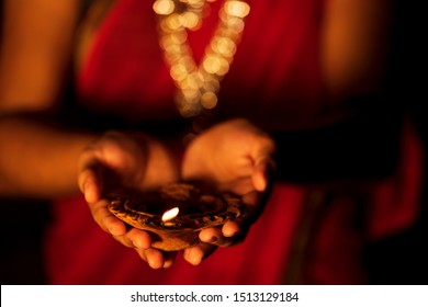 Happy Diwali - A beautiful woman or housewife holding a diya. Newly wed bride wearing traditional saree & jewellery with terracotta oil lamp on her hand during diwali celebration.