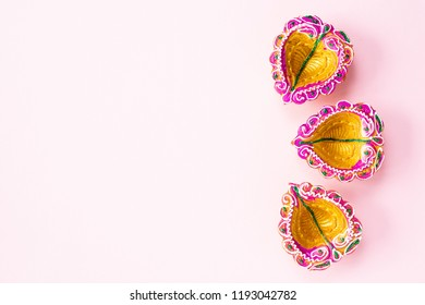Happy Diwali - Clay Diya lamps lit during Dipavali, Hindu festival of lights celebration. Colorful traditional oil lamp diya on pink background
