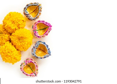 Happy Diwali - Clay Diya lamps lit during Dipavali, Hindu festival of lights celebration. Colorful traditional oil lamp diya with yellow flower on white background