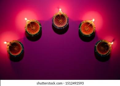 Happy Diwali - Clay Diya lamps lit during Dipavali, Hindu festival of lights celebration. Colorful traditional oil lamp diya on pink background