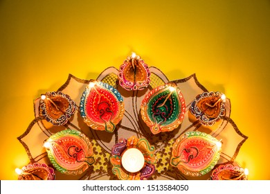 Happy Diwali - Clay Diya lamps lit during Dipavali, Hindu festival of lights celebration. Colorful traditional oil lamp diya on yellow background