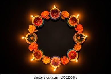 Happy Diwali - Clay Diya lamps lit during Dipavali, Hindu festival of lights celebration. Colorful traditional oil lamp diya on black background