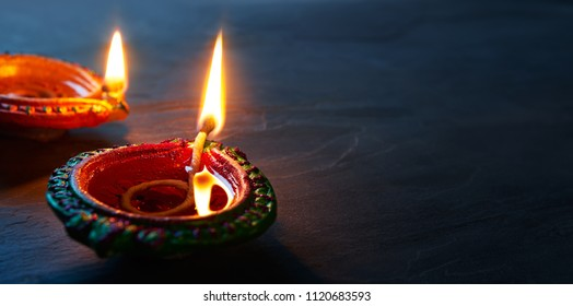 Happy Diwali - Close up of lit Diya lamps on floor