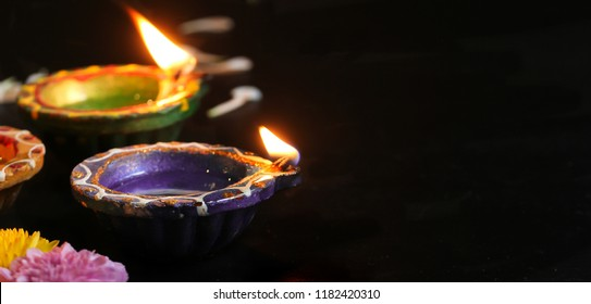 Happy Diwali - Colorful Clay Diya lit during Deepavali festival of lights, selective focus