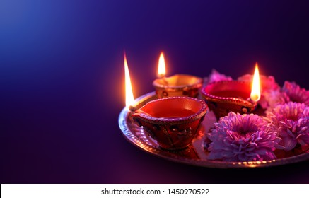 Happy Diwali - Colorful clay diya lamps lit during diwali celebration with copy space
