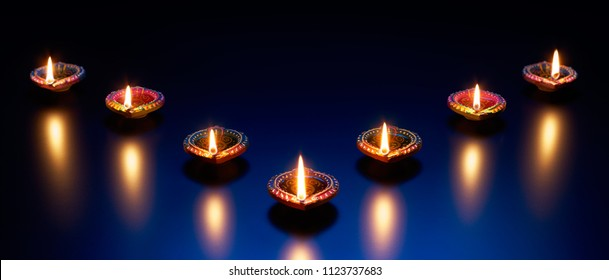 Happy Diwali - Diya lamps on a reflective base