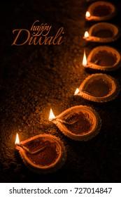 Happy Diwali greeting card design using Beautiful Lit Diya OR Clay oil lamps. Selective focus
