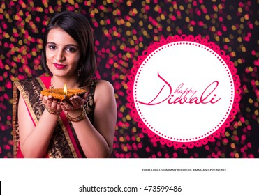 happy diwali greeting card showing indian beautiful Girl holding a diya or Terracotta Oil Lamp over black background