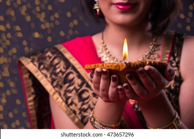 Happy Diwali Greeting card showing indian beautiful Girl holding a diya over black background