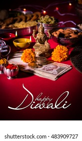 Happy Diwali Greeting card showing oil lamp / diya with fire crackers, Mithai, dry fruits, indian currency notes, marigold flower and statue of Goddess Laxmi or Lakshmi