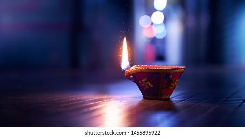 Happy Diwali - Lit diya lamp on street at night