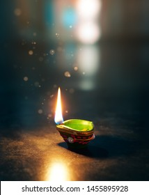 Happy Diwali - Lit diya lamp on an abtract background with shallow depth of field