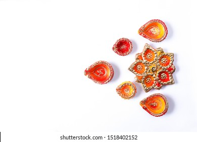 Happy Diwali - many colorful Terracotta diya or oil lamps arranged over white surface or ground in one line or curved or zigzag form, Colorful Diya on white background.