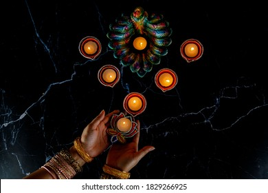 Happy Diwali - Woman hands with henna holding lit candle isolated on dark background. Clay Diya lamps lit during Dipavali, Hindu festival of lights celebration. Copy space for text.