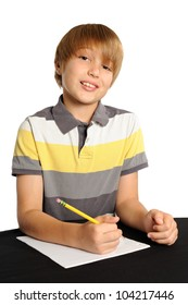 Happy to do Homework. Nine year-old boy sitting at a table with his pencil ready to do homework or take a test. Isolated on white.