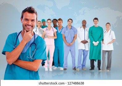 Happy doctor with medical staff behind him on world map background