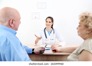 Happy doctor and patients in hospital clinic