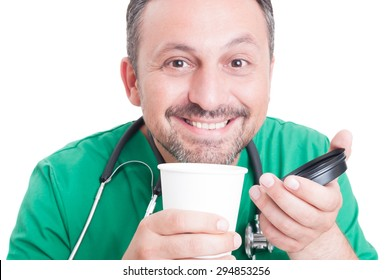 Happy doctor smiling and enjoying fresh coffee from disposable cup