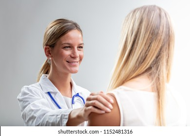 Happy doctor smiling as she gives good news to a blond woman standing with her back to the camera in an over the shoulder view
