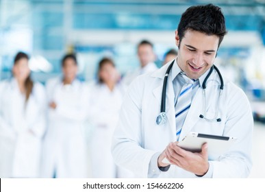 Happy doctor using tablet computer at the hospital