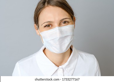 Happy doctor wearing surgical mask with confidence in the future to solve the crisis. Isolated on gray background