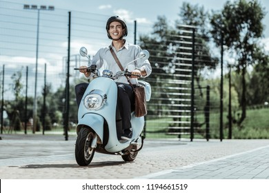 Happy driver. Low angle of joyful male student grinning in helmet and driving motorbike