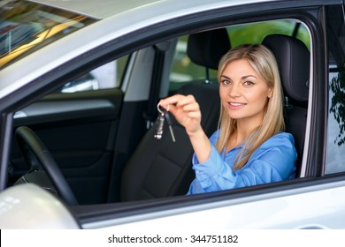 Happy driver. Pleasant smiling delighted female sale assistant sitting in the car and going to  test it while holding keys in  hands