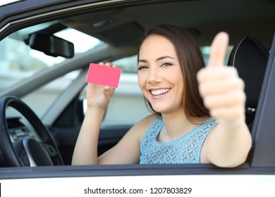 Happy driver showing a blank card or license with thumbs up inside a car